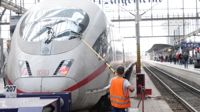 railway employee cleans the windscreen of an arrived train while passengers board the arriving train at frankfurter bahnhof or leave the station on... - bahnreisender stock-videos und b-roll-filmmaterial