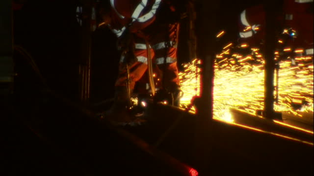 Railway engineers performing repairs and maintenance at night using cutting torch to cut tracks