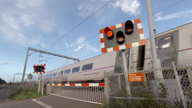 railway level crossing gates closed with a train passing - level crossing stock videos & royalty-free footage