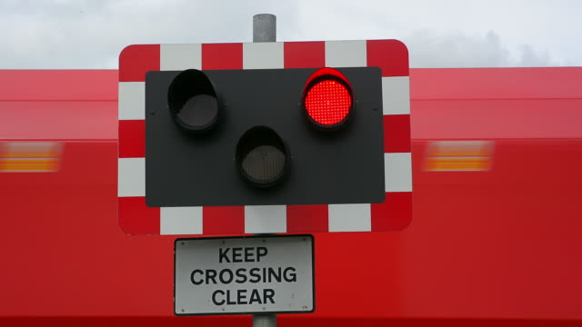 vídeos y material grabado en eventos de stock de railway level crossing gates closing and freight train passing. - export palabra en inglés