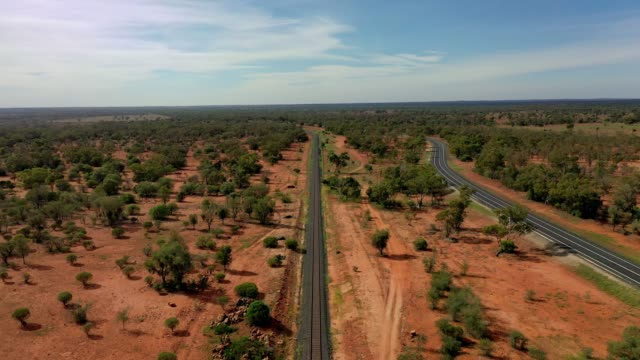 railway track and highway, country road, red dirt and blue sky, rural australia - cargo train stock videos & royalty-free footage