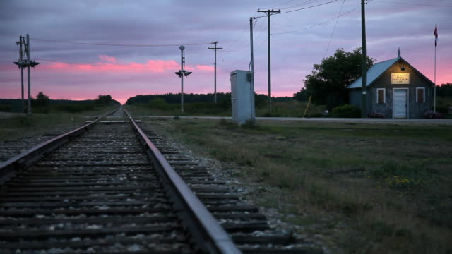 a railway with a pinky sunset in the background - マニトバ州点の映像素材/bロール