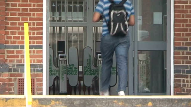 railway worker suspended after jumping onto tracks to save disabled passenger; departure board inside station see through open door at entrance... - segnale informativo video stock e b–roll