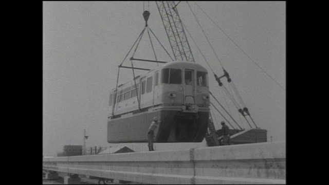 railway workers supervise as a tokyo monorail car is lowered onto the monorail at showajima works. - monorail stock videos & royalty-free footage