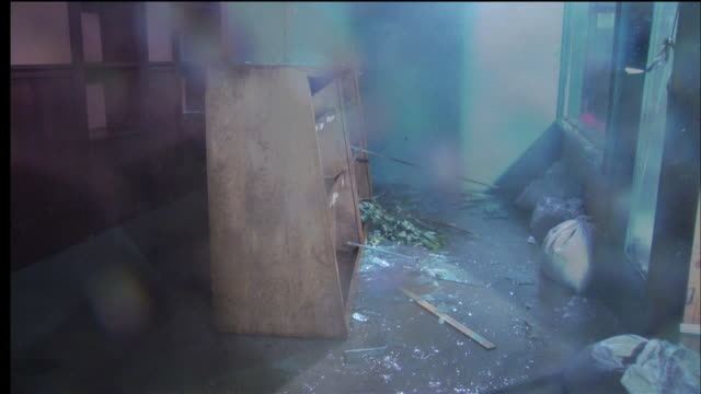 stockvideo's en b-roll-footage met rain and debris blow through a broken window during a violent storm. - stroomuitval