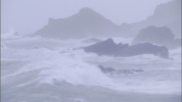 vídeos de stock e filmes b-roll de rain and mist limits visibility as storm waves break against coastal boulders and cliffs. - penedo