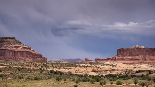 rain and sunlight between buttes in canyonlands national park - time lapse - canyonlands national park stock videos & royalty-free footage