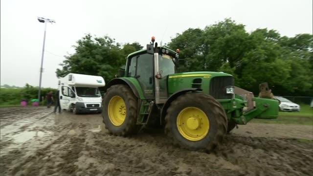 rain at glastonbury festival goers along past tents / tractor pulls caravan out of the mud - festzelt stock-videos und b-roll-filmmaterial