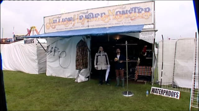 vídeos de stock, filmes e b-roll de rain disrupts isle of wight festival england isle of wight ext cook with a tin over their head along in rain / festival banners blowing pull out... - golf cart