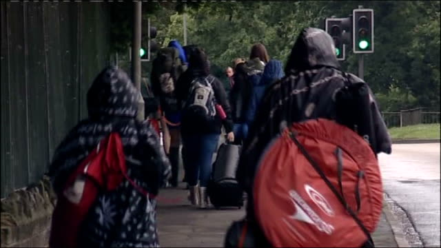 stockvideo's en b-roll-footage met rain disrupts isle of wight festival; queue of traffic / vehicles including bus in traffic jam / people carrying camping gear towards / man and woman... - festivalganger