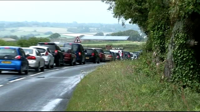 rain disrupts olympic torch relay and isle of wight festival; england: isle of wight: ext traffic jam along country road - traffic jam点の映像素材/bロール