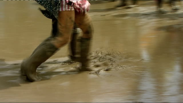 rain disrupts olympic torch relay and isle of wight festival isle of wight festivalgoers walking through mud in wellingtons at isle of wight festival - stiefel stock-videos und b-roll-filmmaterial