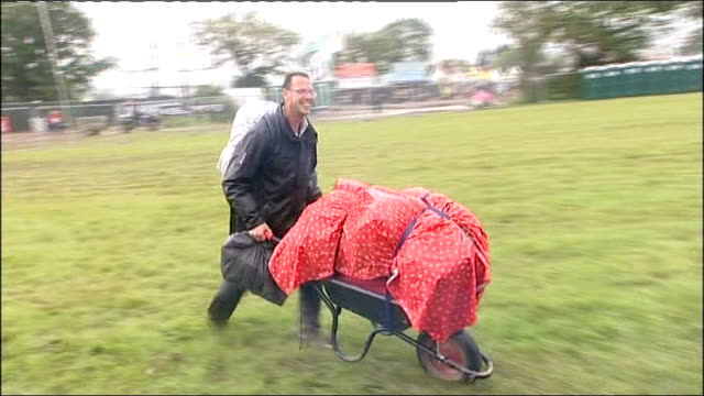 rain disrupts olympic torch relay and isle of wight festival raining man pushing wheelbarrow across field three women along wearing clear anoraks - waterproof clothing stock videos & royalty-free footage