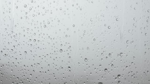 vidéos et rushes de goutte de pluie sur le verre de fenêtre - verre translucide