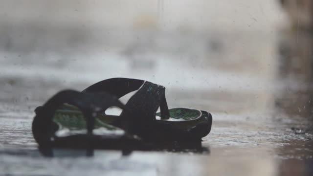 vídeos de stock, filmes e b-roll de a chuva cai pingando na calçada, em câmera lenta. - nível da superfície