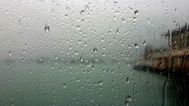 vidéos et rushes de gouttes de pluie ruisselant sur le verre de fenêtre - verre translucide