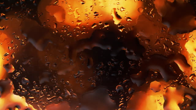 rain drops falling from glass window at fire background - black colour stock videos & royalty-free footage