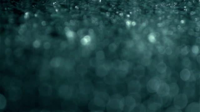 Rain drops falling into ground, slow motion