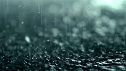 Rain drops falling into ground, slow motion