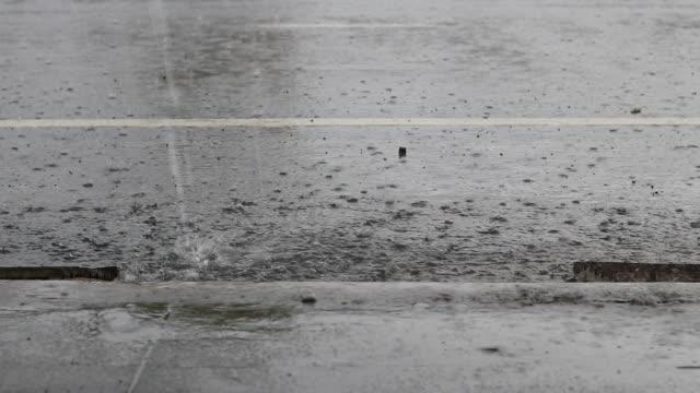 vídeos de stock, filmes e b-roll de respingos de gotas de chuva sobre a estrada de asfalto. - forma da água