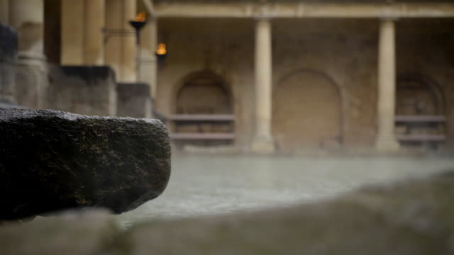 Rain falling and steam rising from The Great Bath at the Roman Bath complex