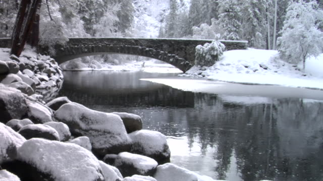 WS Rain falling in river near stone footbridge in Yosemite National Park / California, USA