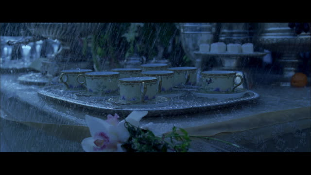 DS Rain falling on a table holding tea cups and a formal tea service