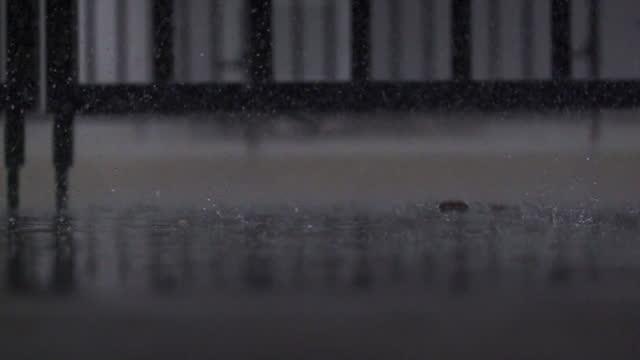 スローモーションで歩道に降る雨。 - サウンドトラック点の映像素材/bロール