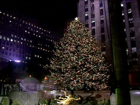 NIGHT Rain falling on Rockefeller Plaza ice skating rink PAN UP lighted tree spot lights roaming plaza tree