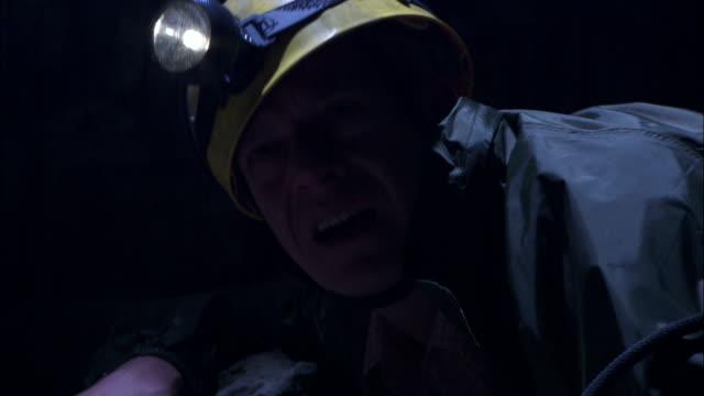vídeos y material grabado en eventos de stock de rain falls around an injured spelunker as he looks around with his flashlight. - accesorio de cabeza
