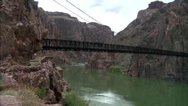 vidéos et rushes de rain falls as the colorado river water flows under a long footbridge. - parc national du grand canyon