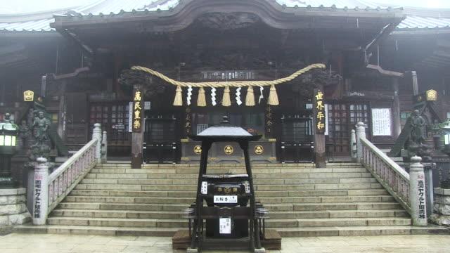 Rain falls on Buddhist temple Takao-san Yakuo-in Yuki-ji on Mount Takao, Japan.