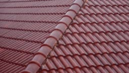 Rain falls on the red roof of the house on a day.