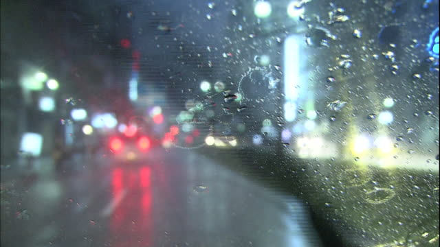 Rain falls on the windshield of a car driving on a city street.
