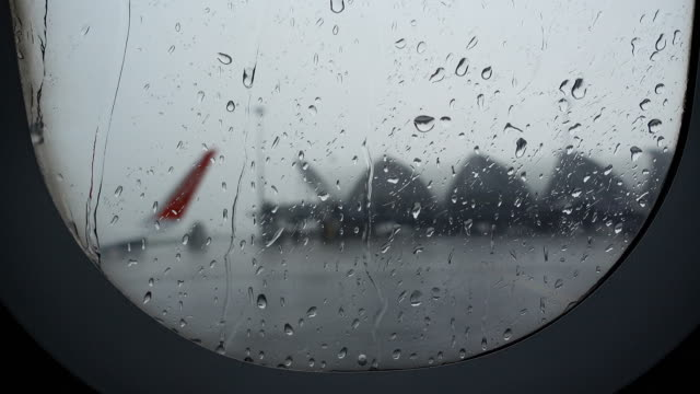 rain flight delays taken from window with airport view - fragility stock videos & royalty-free footage