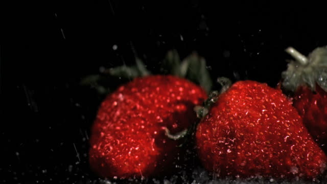Rain in super slow motion falling on strawberries