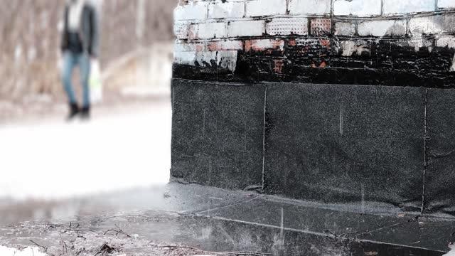 vidéos et rushes de la pluie tombe sur le sol humide à côté du mur de briques. l'homme méconnaissable passe sur l'arrière-plan - sale