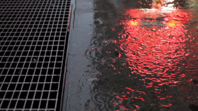 rain on sidewalk with grate and reflected neon light