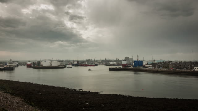 a rain shower and darkening skies passover aberdeen's busy industrial harbour with the city skyline in the distance - passover stock videos and b-roll footage