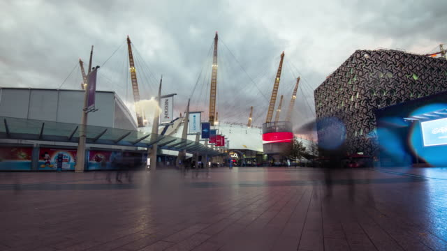 vídeos de stock e filmes b-roll de a rain shower passes as evening arrives and the sky darkens crowds of people arrive and travelled through the peninsula square towards the o2 entertainment complex a multipurpose indoor arena on the greenwich peninsula in central london - parede de vídeo