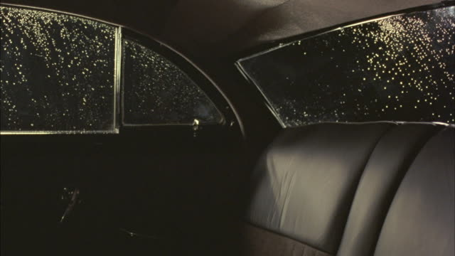 Rain spatters against the windows of a vintage car.