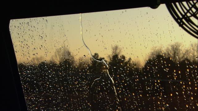 vidéos et rushes de rain splashes down the windshield of a truck while the driver grips the steering wheel. - mouillé