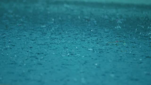 rain water droplets splash into a blue puddle - raindrop stock videos & royalty-free footage