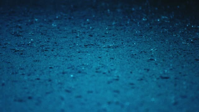 rain water droplets splash into a blue puddle - rain stock videos & royalty-free footage