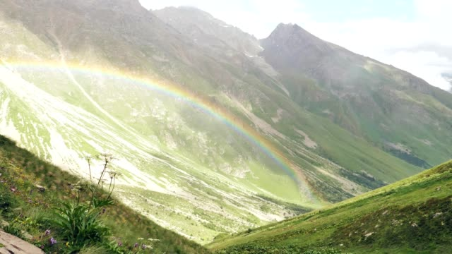 rainbow above mountain valley. caucasus mountains - mountain pass stock videos & royalty-free footage