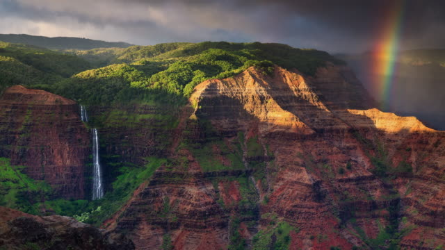 t/l rainbow and clouds over waipoo falls in waimea canyon state park - isola di kauai video stock e b–roll