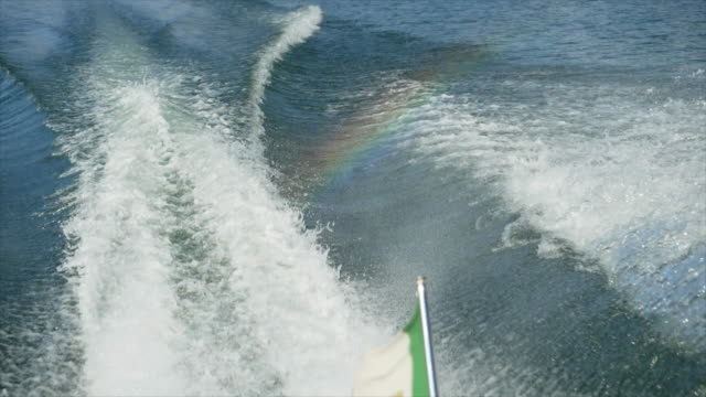 a rainbow and wake from a classic luxury wooden runabout boat on an italian lake. - slow motion - 唯一点の映像素材/bロール