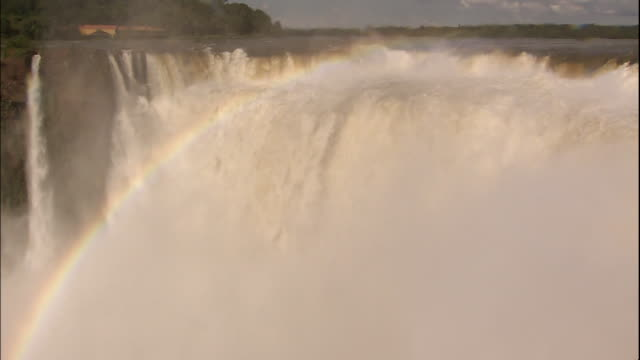 rainbow appears in mist of water pouring over devil's throat section of iguazu falls, border of brazil and argentina - devil's throat stock videos and b-roll footage