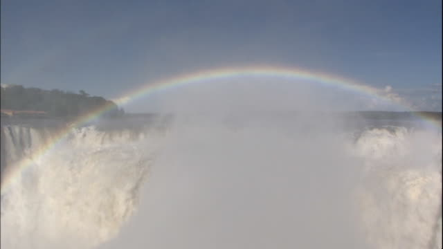 rainbow appears in mist rising from devil's throat section of iguazu falls, border of brazil and argentina - 50 seconds or greater stock videos & royalty-free footage