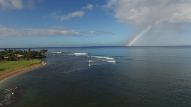 A rainbow appears over a Hawaiian surf break on Kauai. This local spot is off the beaten path but surfers find perfect waves under the rainbow.